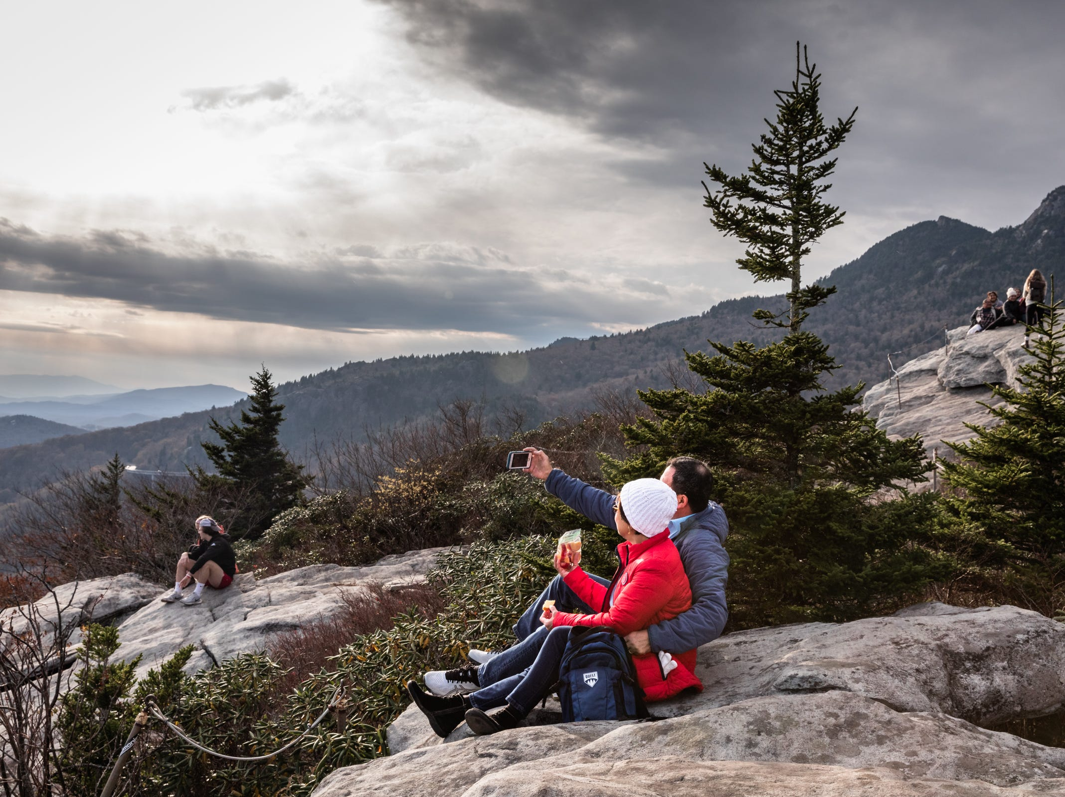 A couple takes a cell phone photograph together while sitting on a rocky outcropping at the Rough Ridge overlook on the Blue Ridge Parkway Oct. 28, 2018.