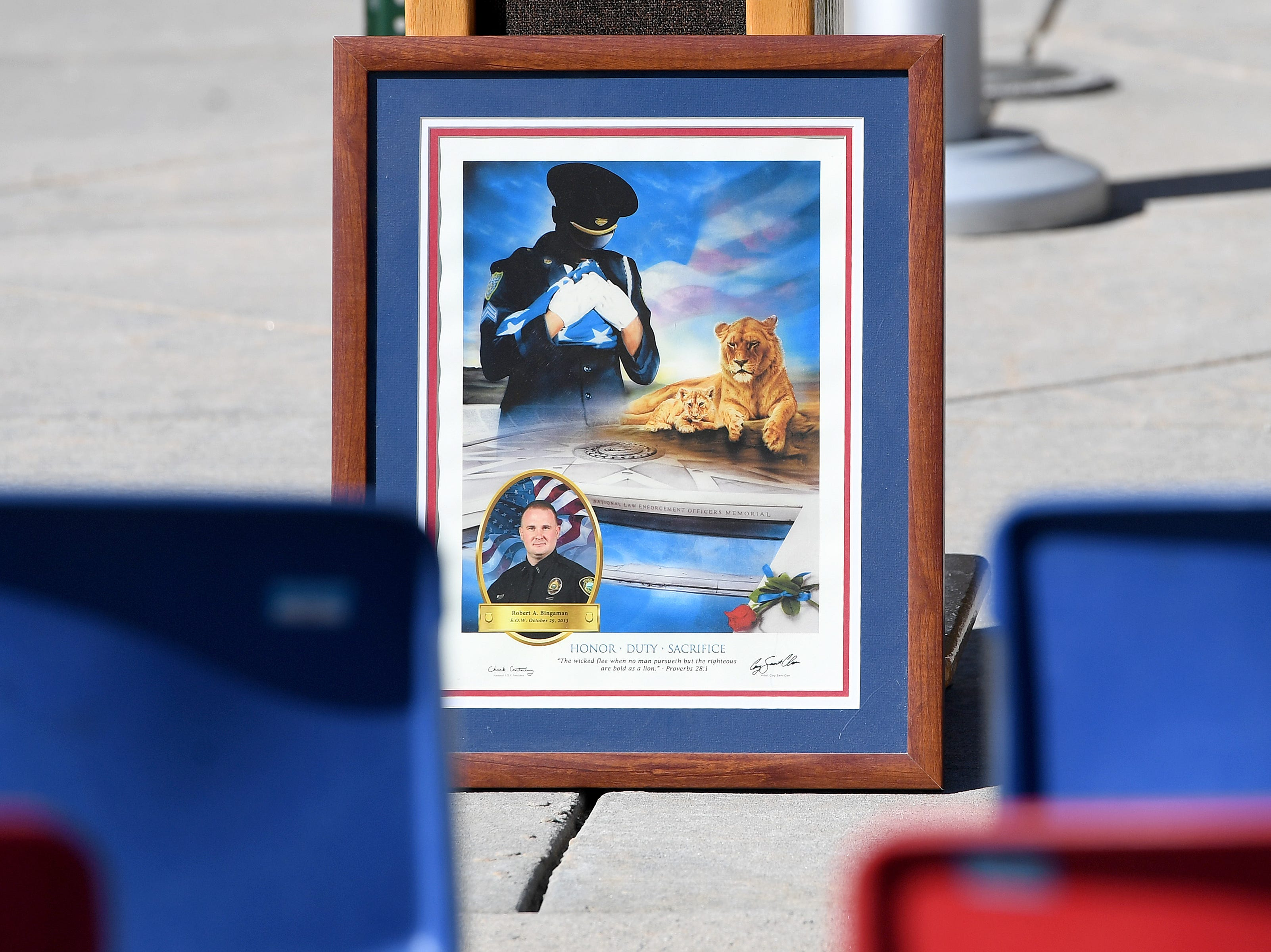 A art piece featuring a photograph of Robert Bingaman leans against the podium before the start of a ceremony at the Traffic Safety Office to dedicate a portion of Old Haywood Road to the Asheville police officer on the five-year-anniversary of his death on Oct. 29, 2018.