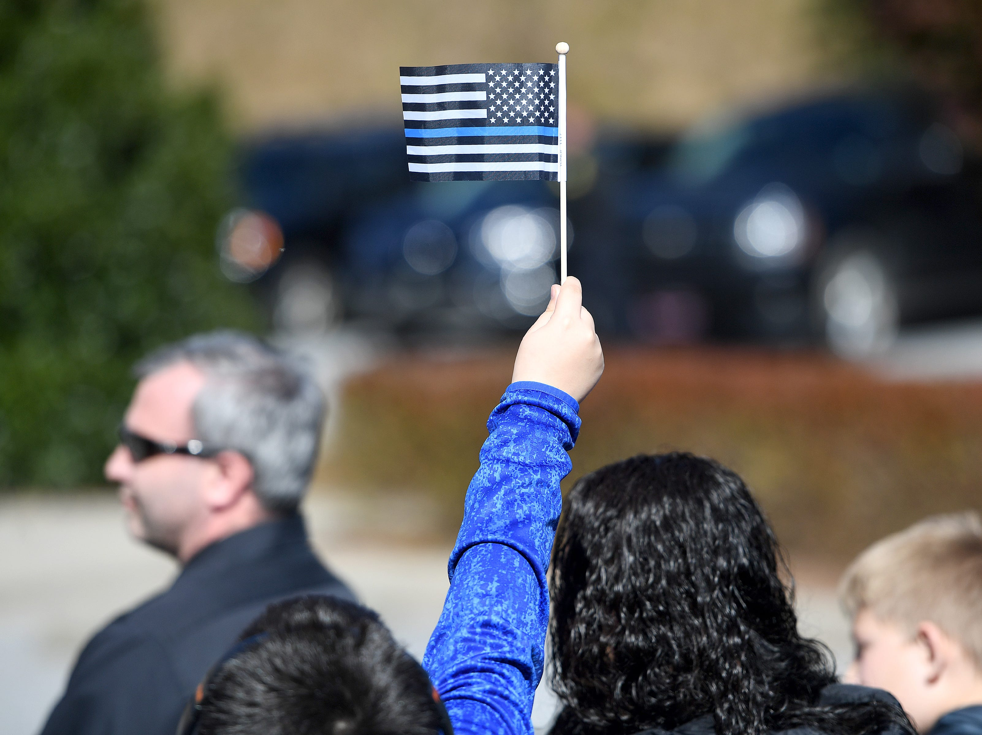 A boy holds a flag during a ceremony to dedicate a portion of Old Haywood Road to Asheville police officer Robert Bingaman at the Traffic Safety Office on the five-year-anniversary of his death on Oct. 29, 2018.