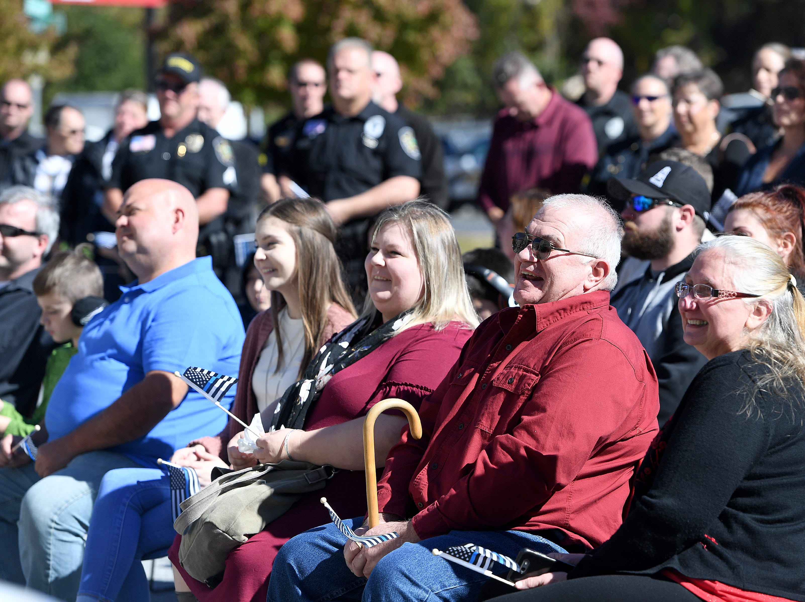 Family members of Robert Bingaman laugh as they remember him during a ceremony to dedicate a portion of Old Haywood Road to the Asheville police officer at the Traffic Safety Office on the five-year-anniversary of his death on Oct. 29, 2018.
