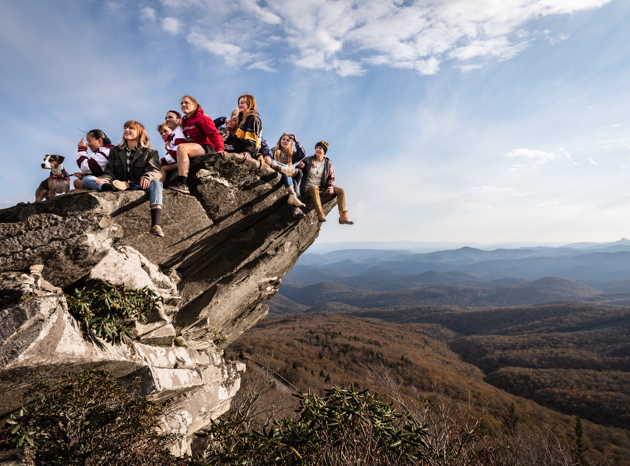 A group of young visitors to the Rough Ridge overlook on the Blue Ridge Parkway pose for a photograph sitting on a rocky overhang Oct. 28, 2018.