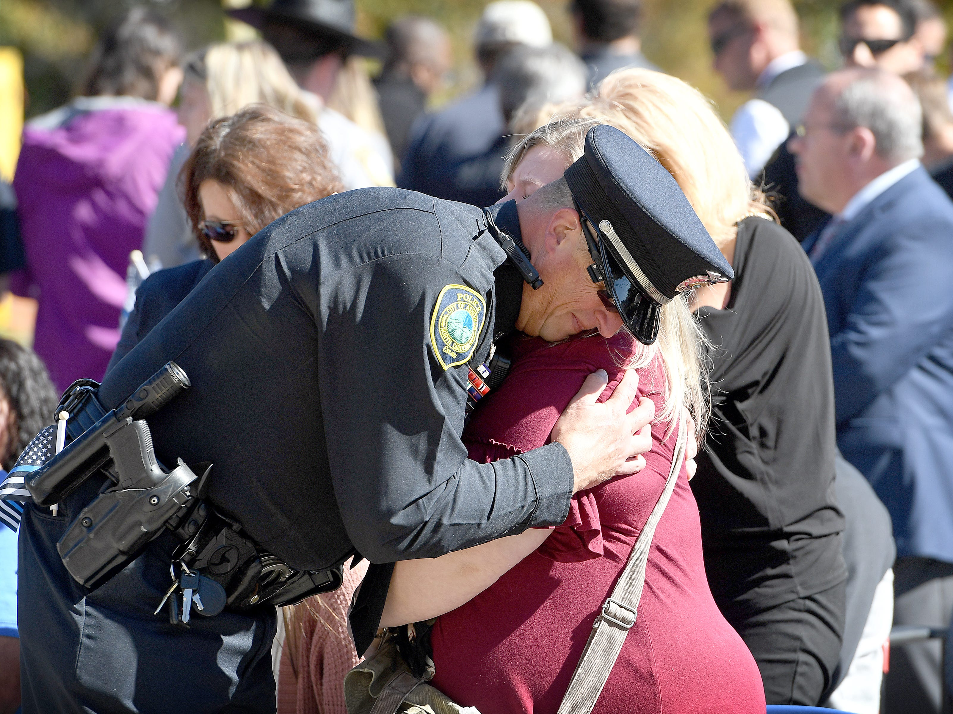 Senior police officer with the Asheville Police Department Scott Fry hugs police officer Robert Bingaman's widow, Genevieve, during a ceremony to dedicate a portion of Old Haywood Road to Bingaman at the Traffic Safety Office on the five-year-anniversary of his death on Oct. 29, 2018.
