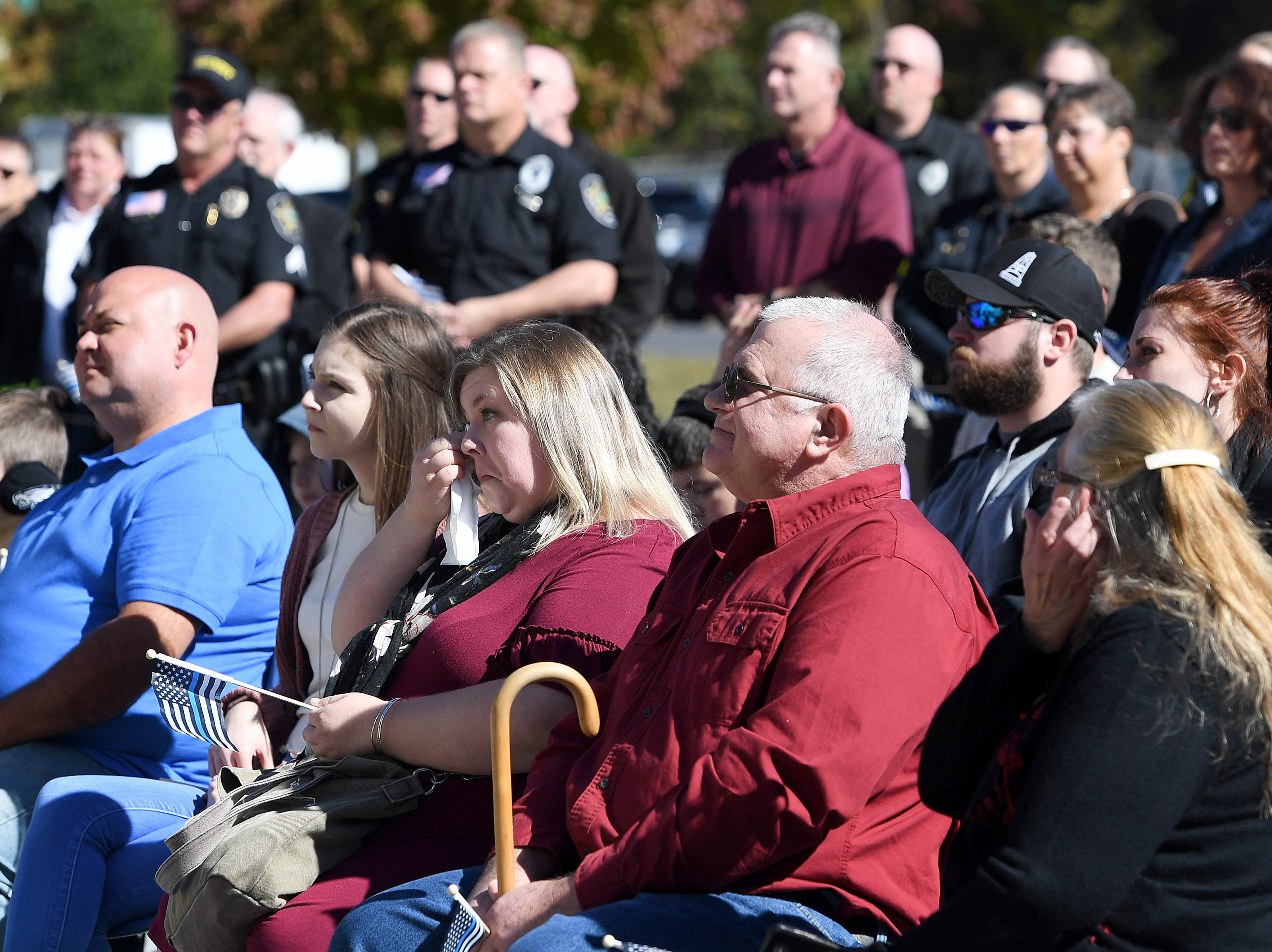 Robert Bingaman's widow Genevieve Ledbetter Bingaman, center, wipes her eyes during a ceremony to dedicate a portion of Old Haywood Road to the Asheville police officer at the Traffic Safety Office on the five-year-anniversary of his death on Oct. 29, 2018.