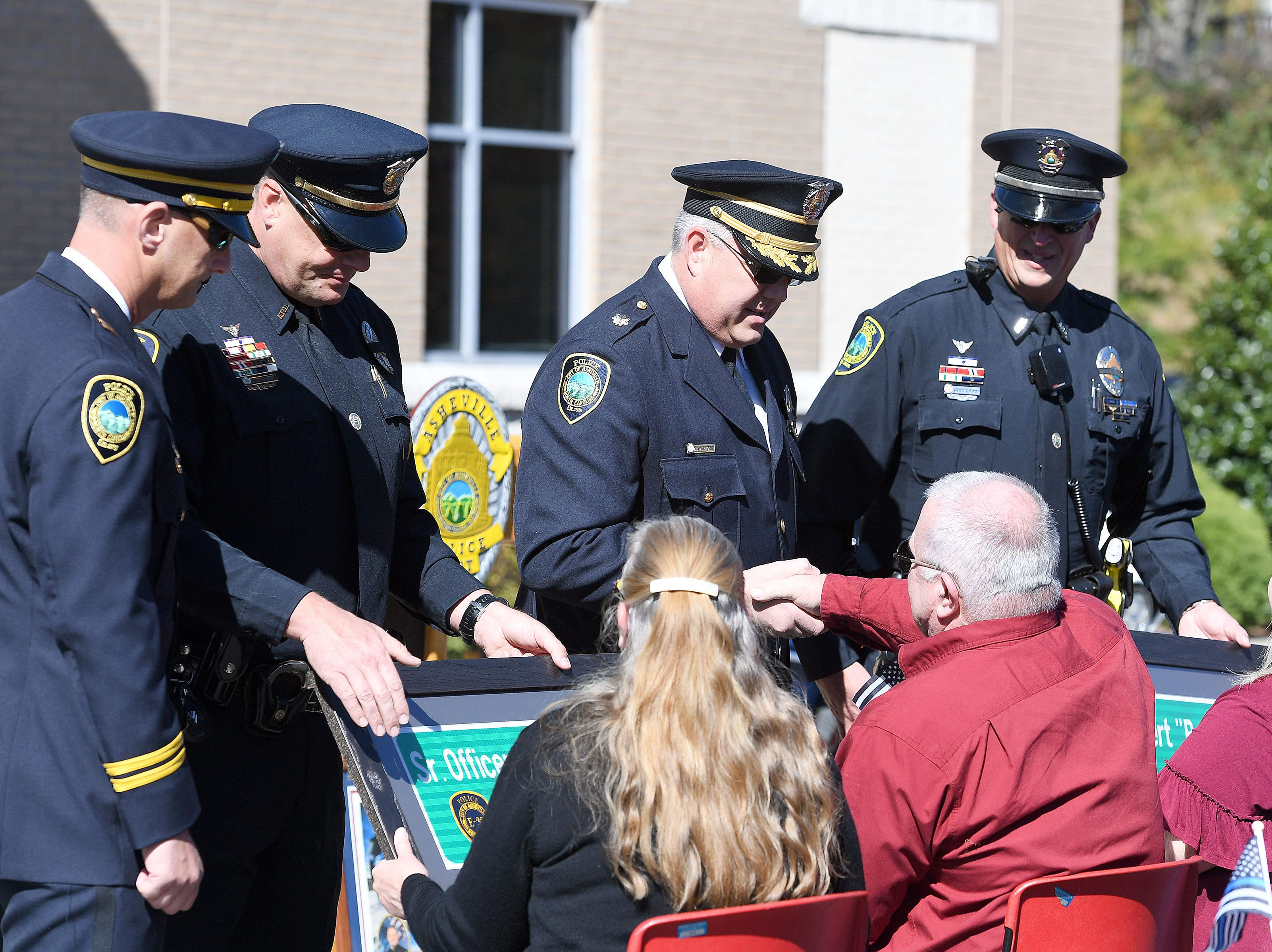 Framed signs mirroring the one that will be placed on Old Haywood Road to dedicate the road to Asheville police officer Robert Bingaman are presented to his parents and widow during a ceremony at the Traffic Safety Office on the five-year-anniversary of his death on Oct. 29, 2018.
