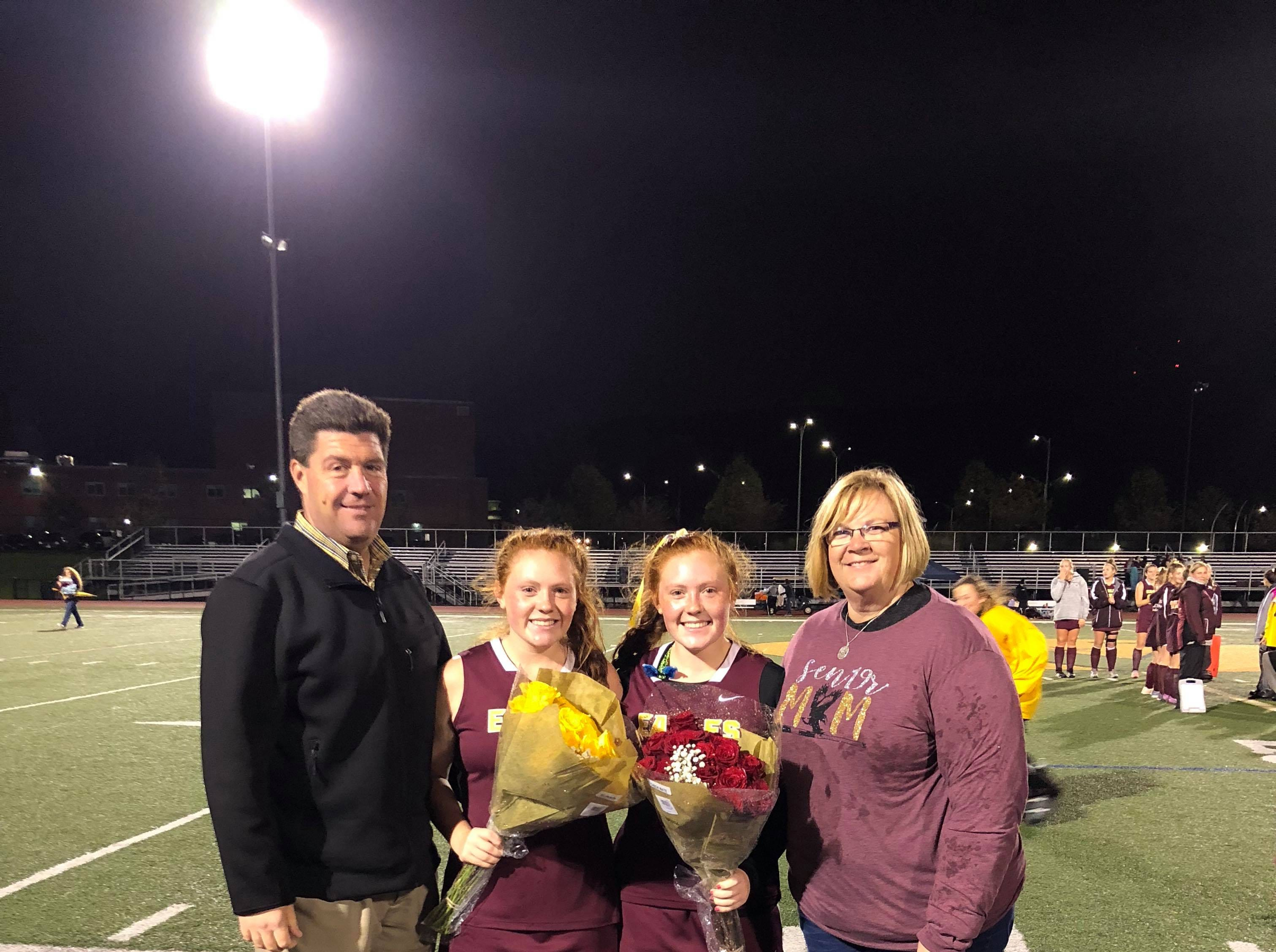Madison Breward (#21), left, and Mary Kate Breward (#13), right, with their parents, Jim and Kelly Breward