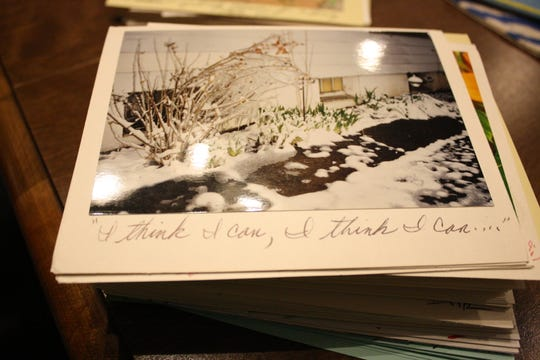 "Hilltop resident David Kacyvenski creates cards using his own photography. Under one photograph, depicting green bulbs bursting through snow, he wrote ""I think I can, I think I can..."""