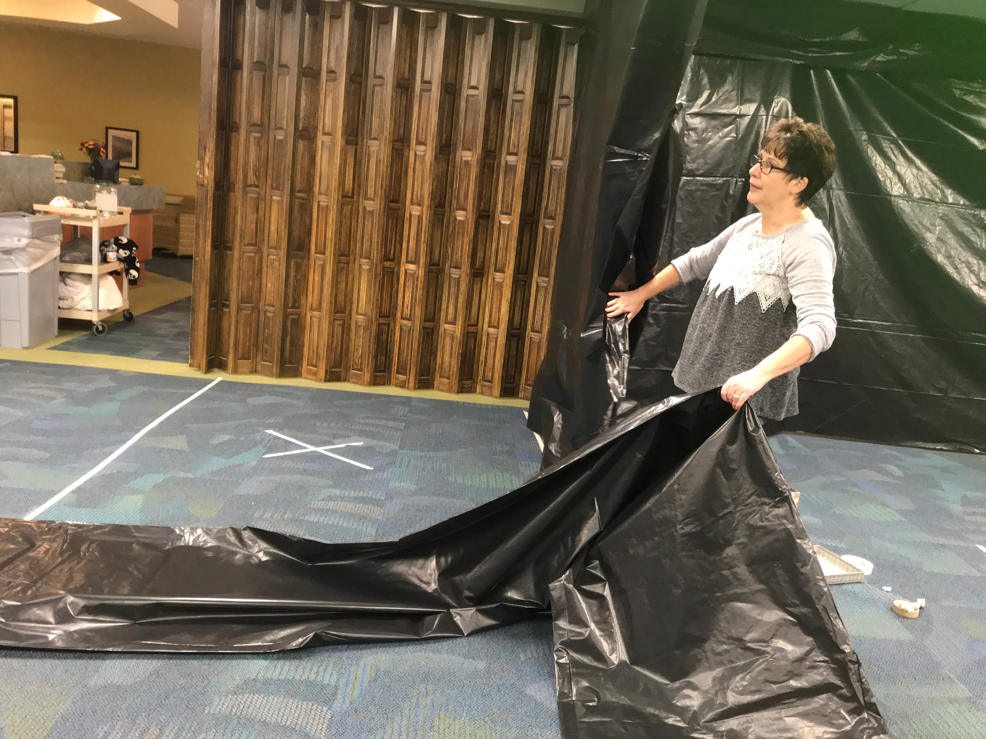 Faye Clark, activity director at Hilltop campus, helps hang black plastic Monday for the community haunted house.