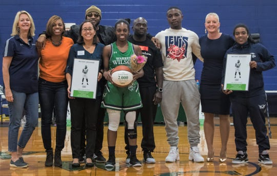 "Surrounded by friends, family and supporters, Danasia ""Piggy"" Dumas receives a ball commemorating her 2,000 career points before the first game of her senior season against Montreat College on Oct. 27."