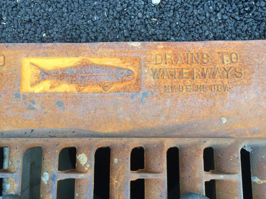 """A storm drain lies adjacent to pavement that allows rainwater to seep into the ground (""""pervious pavement"""") in Burlington on July 9, 2014."""