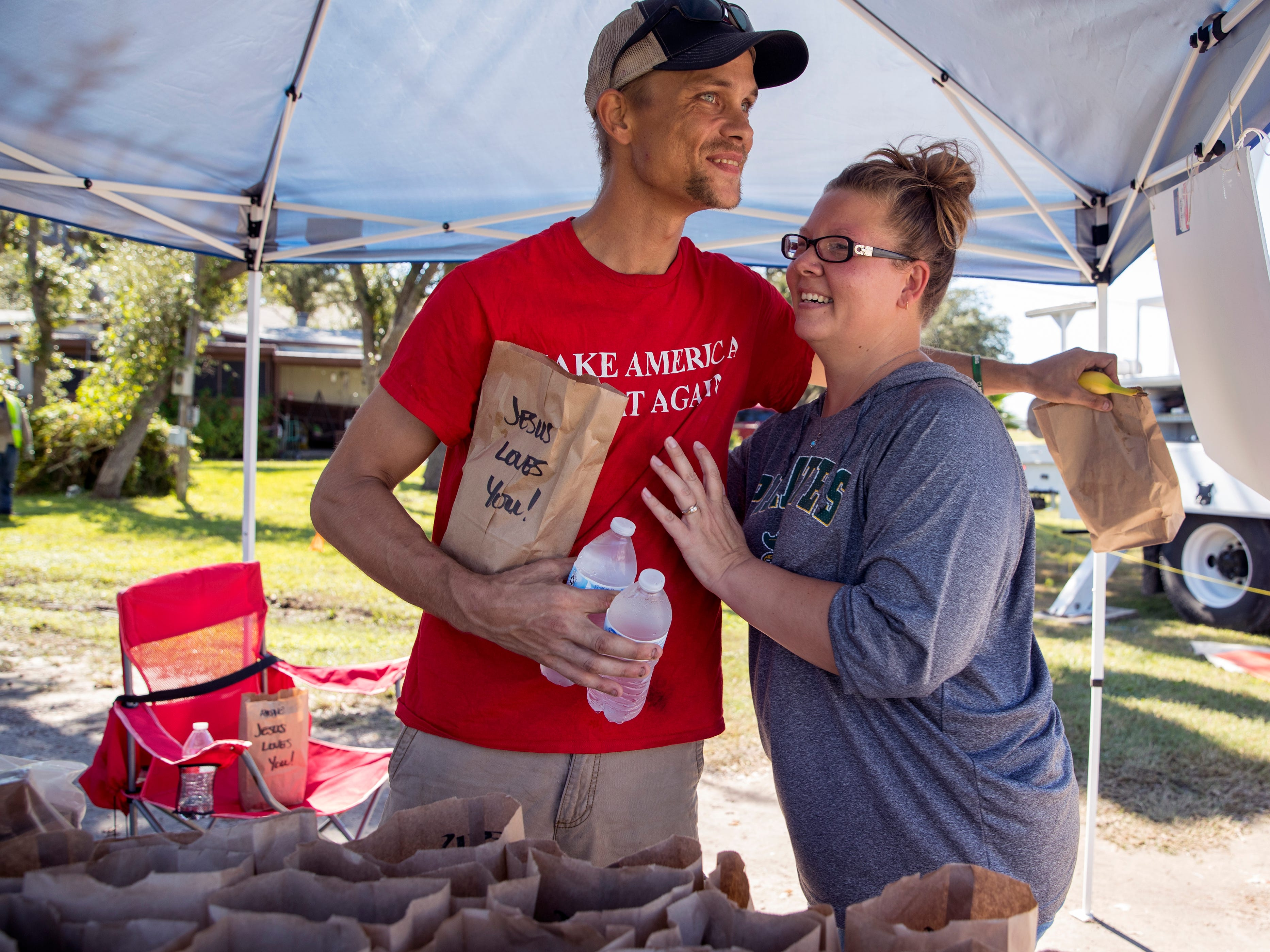 Justin Black (left) gives DeeDee Kilough a hug as he picks up sack lunches from Klough at her home in Rockport on on Monday, October 29, 2018. It is the second time she has given away lunches and said it was a way for her to give back to the community. She posts the information on Facebook and flags down people in passing vehicles to give the lunches away.
