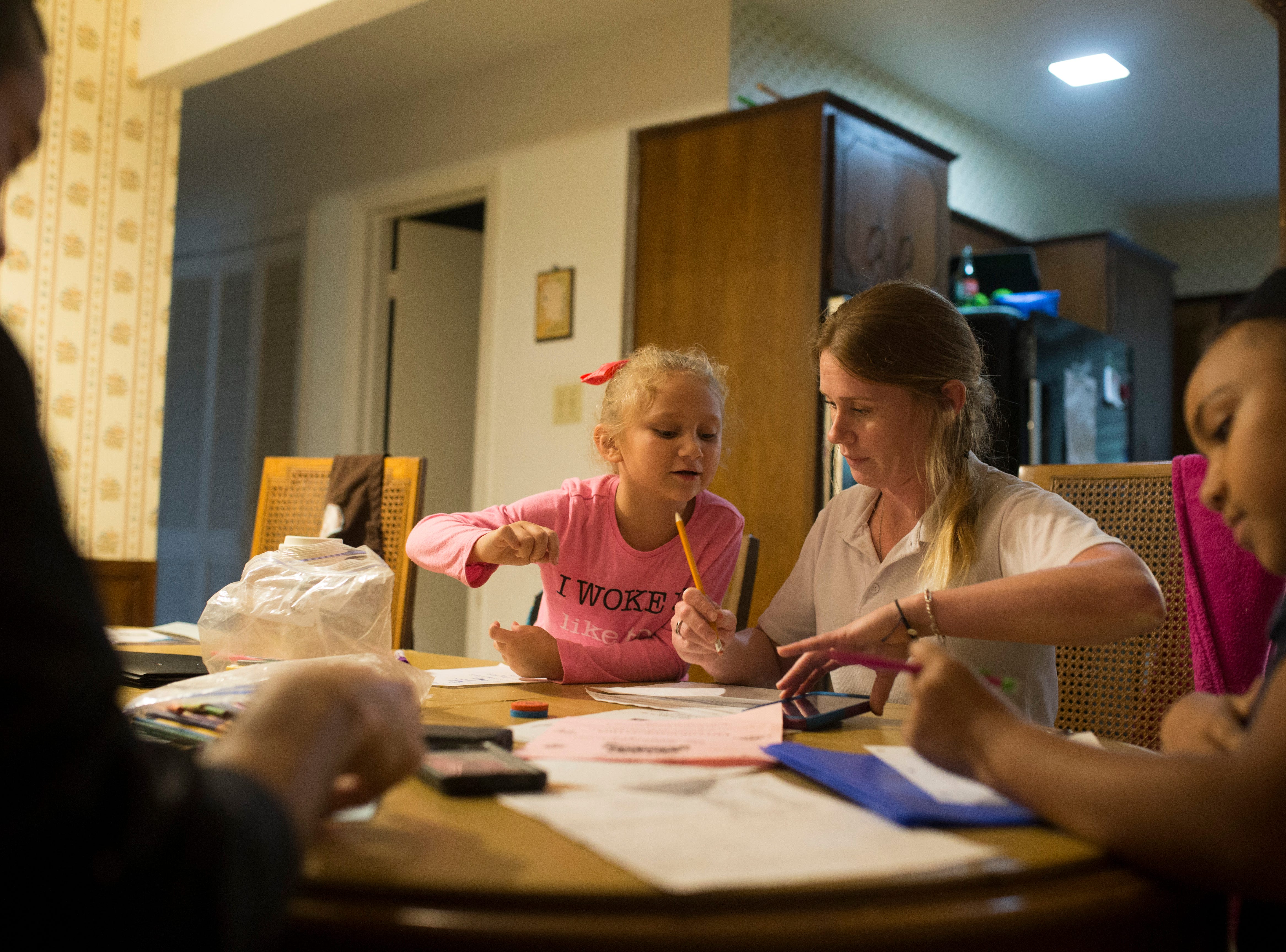 Karah Walters (center) helps her daughter with her homework on Wednesday, Oct. 24, 2018 in Corpus Christi. Walters struggled with drug addiction for years before she sought help and got sober.