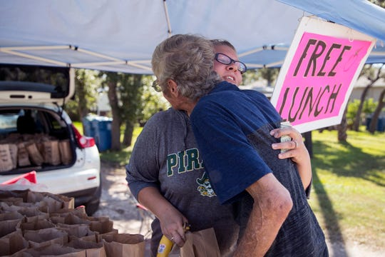 Dough Monroe gives DeeDee Kilough a hug as he picks up a sack lunch at her home in Rockport on on Monday, October 29, 2018. It is the second time Klough has given away lunches and said it was a way for her to give back to the community. She posts the information on Facebook and flags down people in passing vehicles to give the lunches away.