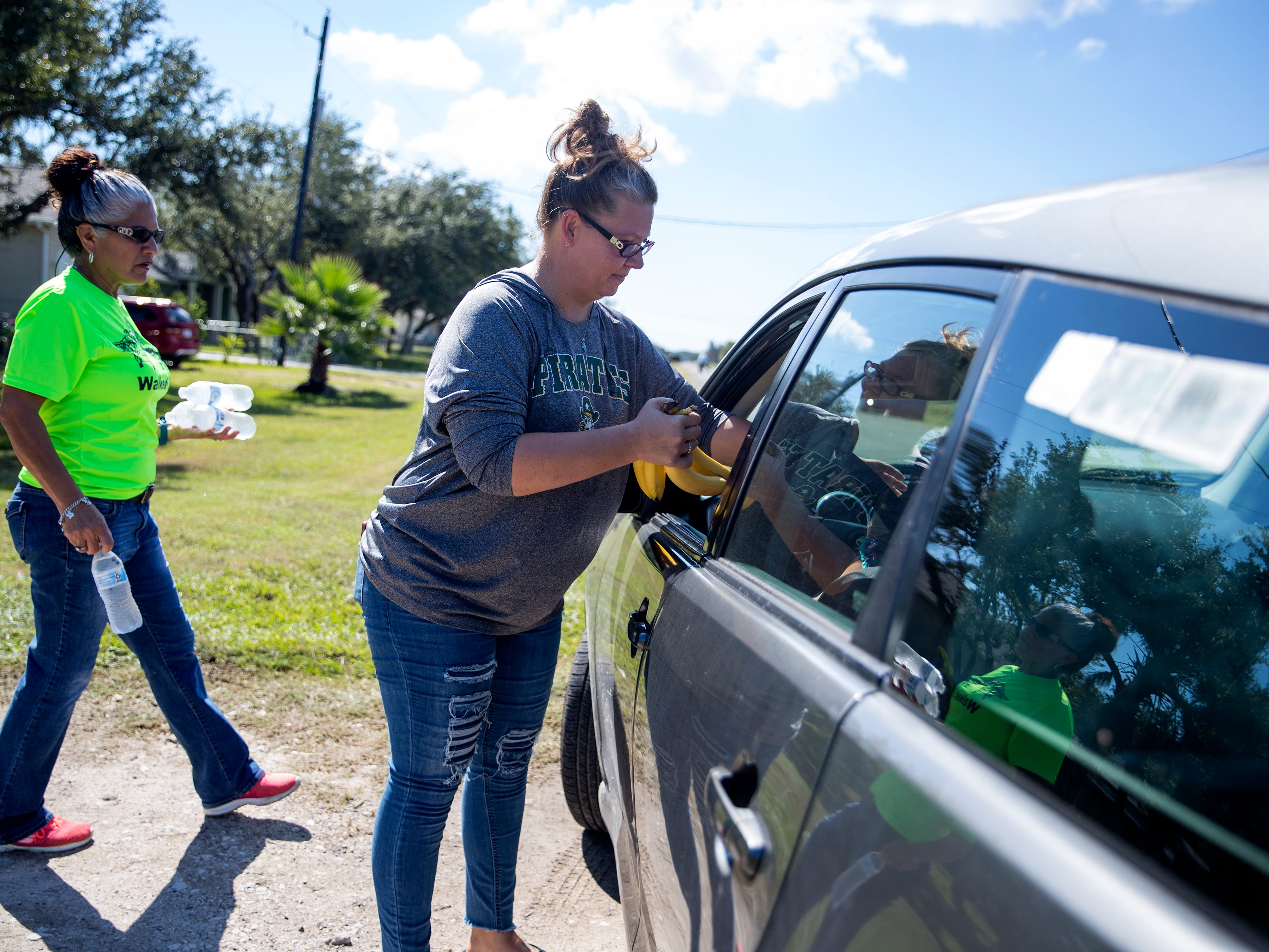 Angie Mendiola (left) and DeeDee Kilough take sack lunches to a woman at Kilough's home in Rockport on on Monday, October 29, 2018. It is the second time Klough has given away lunches and said it was a way for her to give back to the community. She posts the information on Facebook and flags down people in passing vehicles to give the lunches away.
