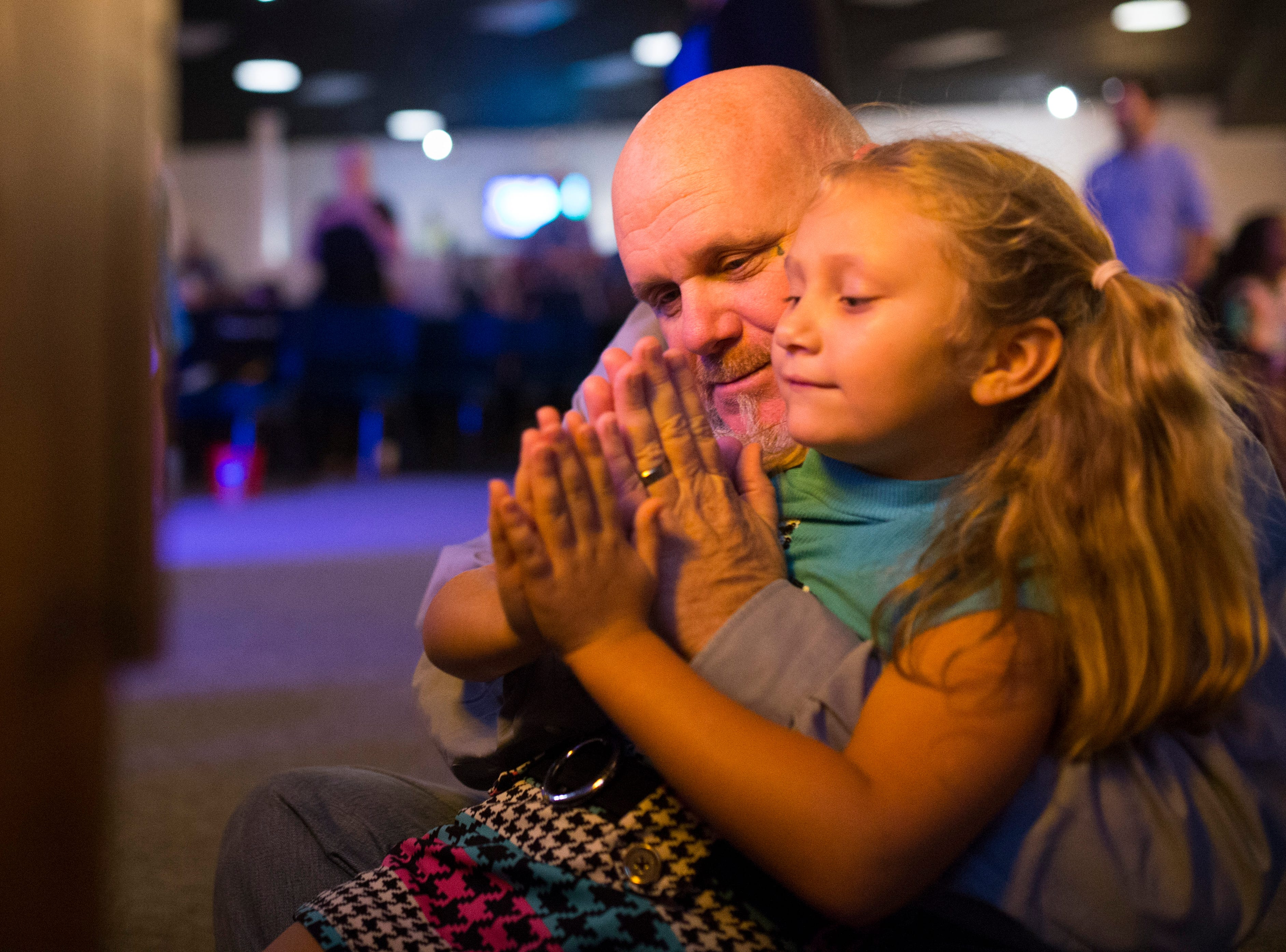 Troy Walters prays at church with his granddaughter on Wednesday, Oct. 24, 2018 in Corpus Christi.  His family has struggled with addiction over the years. Now he's a drug counselor for South Texas Substance Abuse Recovery Services.