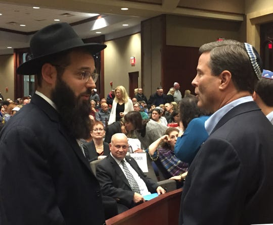Rabbi Yisrael Davidowitz speaks with U.S. Rep. Donald Norcross, D-Camden, at a Voorhees vigil Sunday night that mourned victims of an anti-Semitic attack.