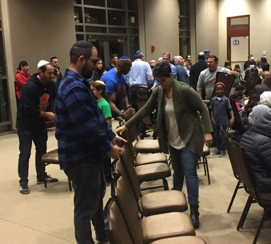 Volunteers put out extra chairs as the crowd grows at a Sunday night vigil in Voorhees for victims of an anti-Semitic attack in Pittsburgh.