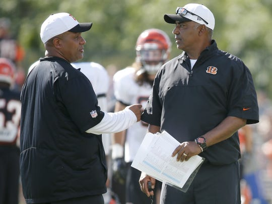 Cincinnati Bengals offensive coordinator Hue Jackson, left, and head coach Marvin Lewis, right, exchange a quick word during Cincinnati Bengals training camp, Wednesday, Aug. 12, 2015, on the practice fields adjacent to Paul Brown Stadium.