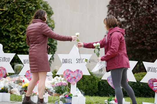 Two women place flowers outside of the Tree of Life Congregation Synagogue in the Squirrel Hill neighborhood of Pittsburgh Monday, October 29, 2018,  after 11 were killed and six other people were wounded Saturday. Robert Bowers allegedly burst into the Tree of Life Congregation Synagogue and screamed anti-Semitic epithets, as he opened fire on the congregants, law enforcement officials said.