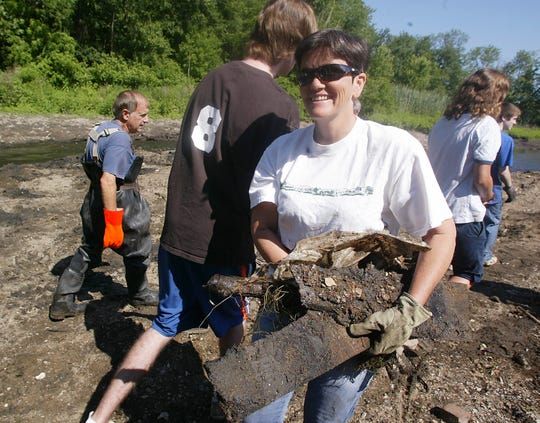 Beth Styler Barry of Asbury, with the Musconetcong Watershed Association, cleaning up at the site of the Gruendyke Mill Dam, which was removed.