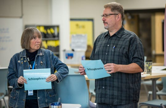 Former teacher and job coach Mary Hilger, left, and teacher Sami El-Baroudi, right, learn the median age range for the onset of certain mental illnesses during a workshop led by Brian Carico and his nephew Michael Cameron, Scavo's school improvement leader, Thursday, Oct. 25, 2018, in Des Moines.