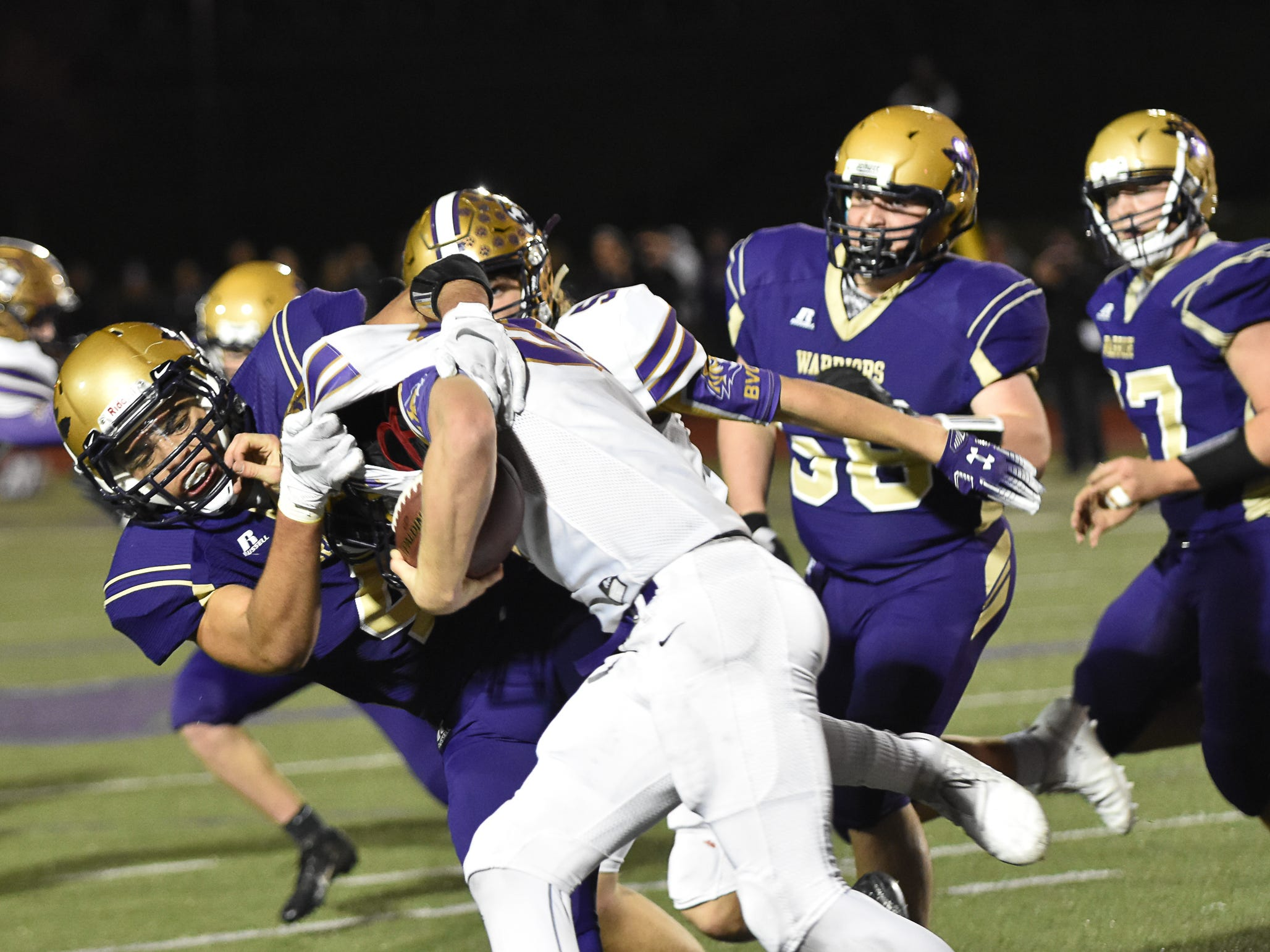 Norwalk's Dylan Wolfe tackles Isaiah Spencer during a first-round playoff game Friday in Norwalk. Spencer ended Norwalk's season Oct. 26, 2018, with a 24-20 win in the first round of the Class 3A playoffs.