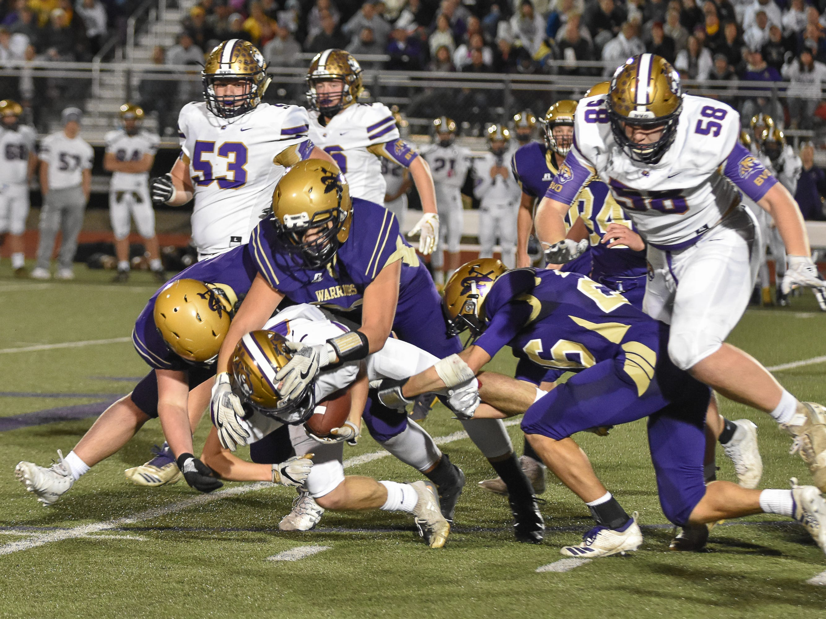 Norwalk's Tyler Robertson, Ethank Stockwell and Carson Raper tackle Spencer's Griffin Garnatz during a first-round playoff game Friday in Norwalk. Spencer ended Norwalk's season Oct. 26, 2018, with a 24-20 win in the first round of the Class 3A playoffs.