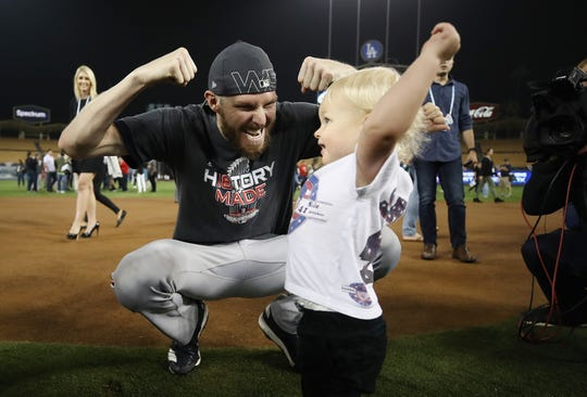 Former FGCU star and current Naples resident Chris Sale (41) of the Boston Red Sox celebrates with his son after his team's 5-1 win over the Los Angeles Dodgers in Game 5 of the 2018 World Series at Dodger Stadium on Oct. 28 in Los Angeles.