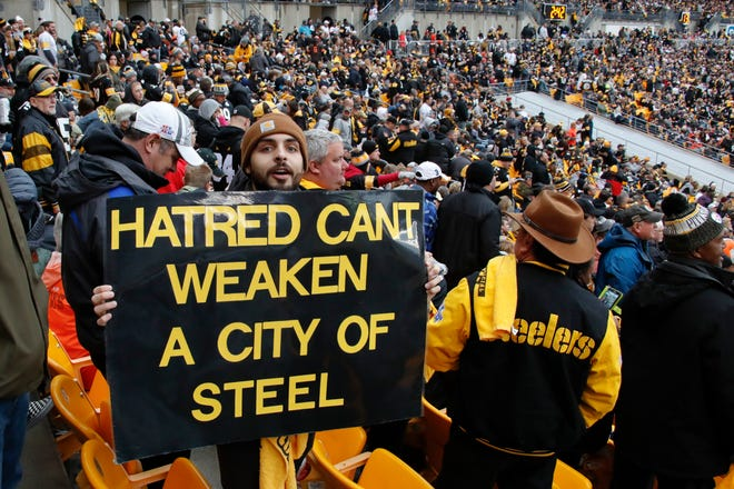 A Pittsburgh Steelers fan holds a sign honoring the victims of a deadly shooting spree at a synagogue on Saturday.