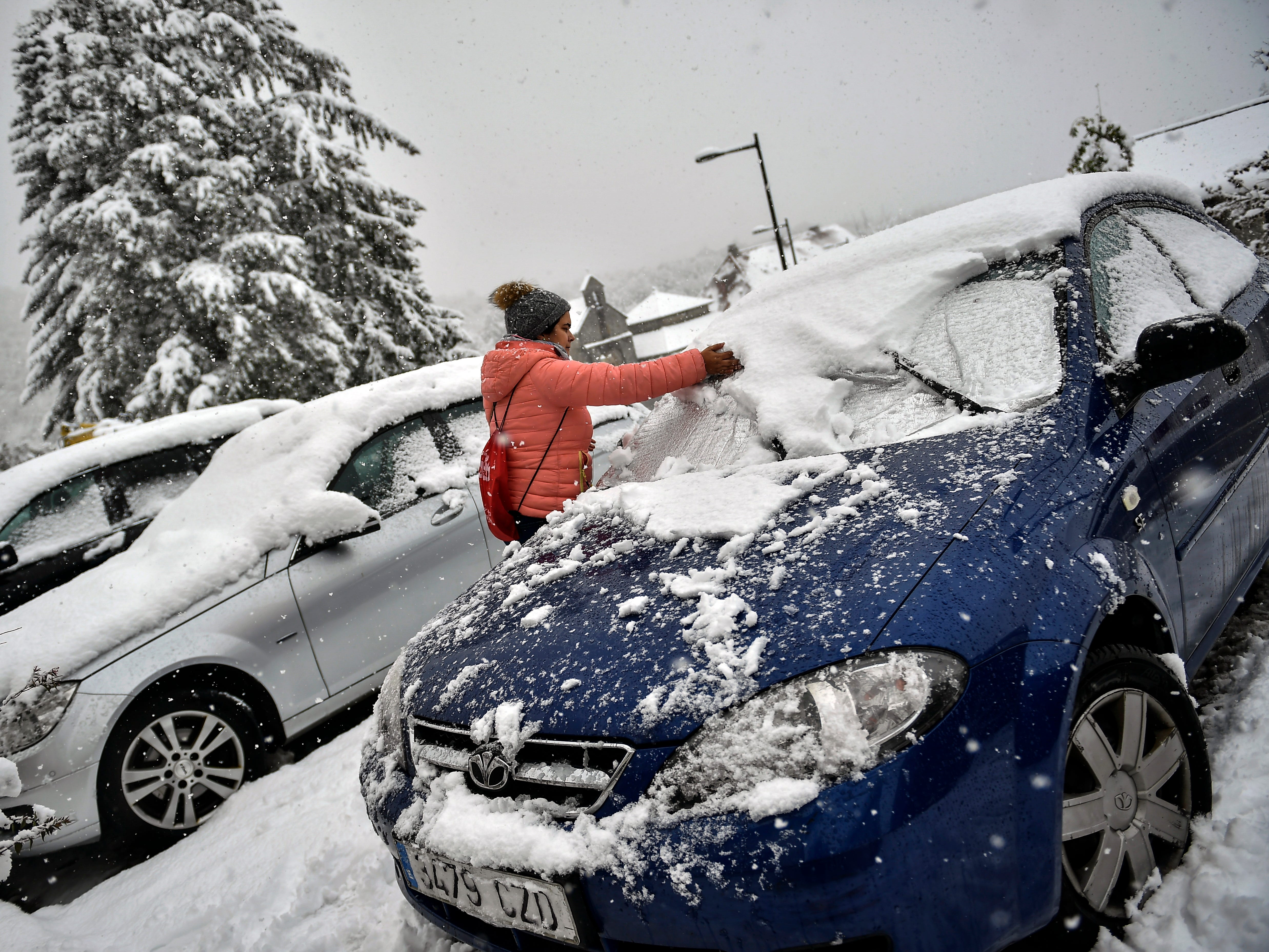 A woman cleans her car covered by the snow during an autumn day, in Roncesvalles, northern Spain, Monday, Oct. 29, 2018. Authorities predict heavy snowfall and extreme low temperatures across Northern Spain this week.