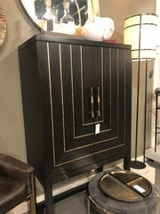 An ebony casegood is highlighted by brass accents. (Design Recipes)