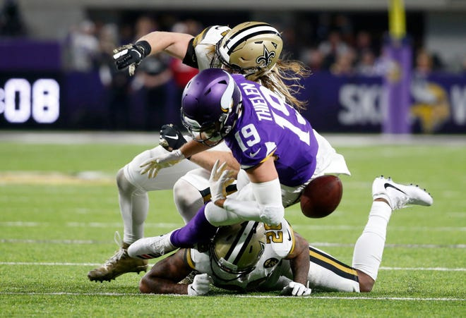 Minnesota Vikings wide receiver Adam Thielen (19) fumbles the ball as he is hit by New Orleans Saints linebacker Alex Anzalone, rear, and cornerback P.J. Williams, bottom, during the first half on Sunday.