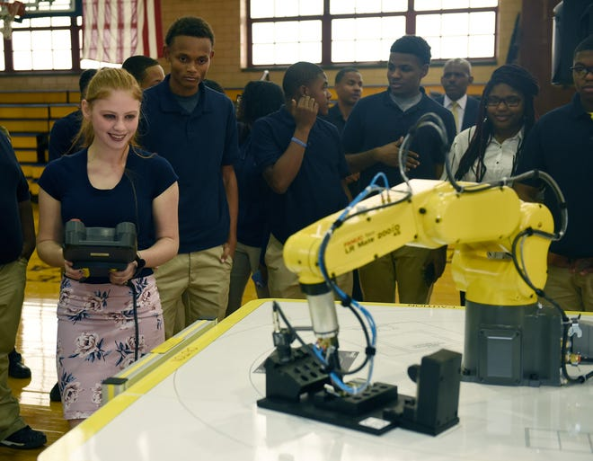 Junior Belann Pillivant, 15, operates the training industrial robot during a demonstration by FANUC America, a leading supplier of robotics and factory automation at Pershing High School Monday.