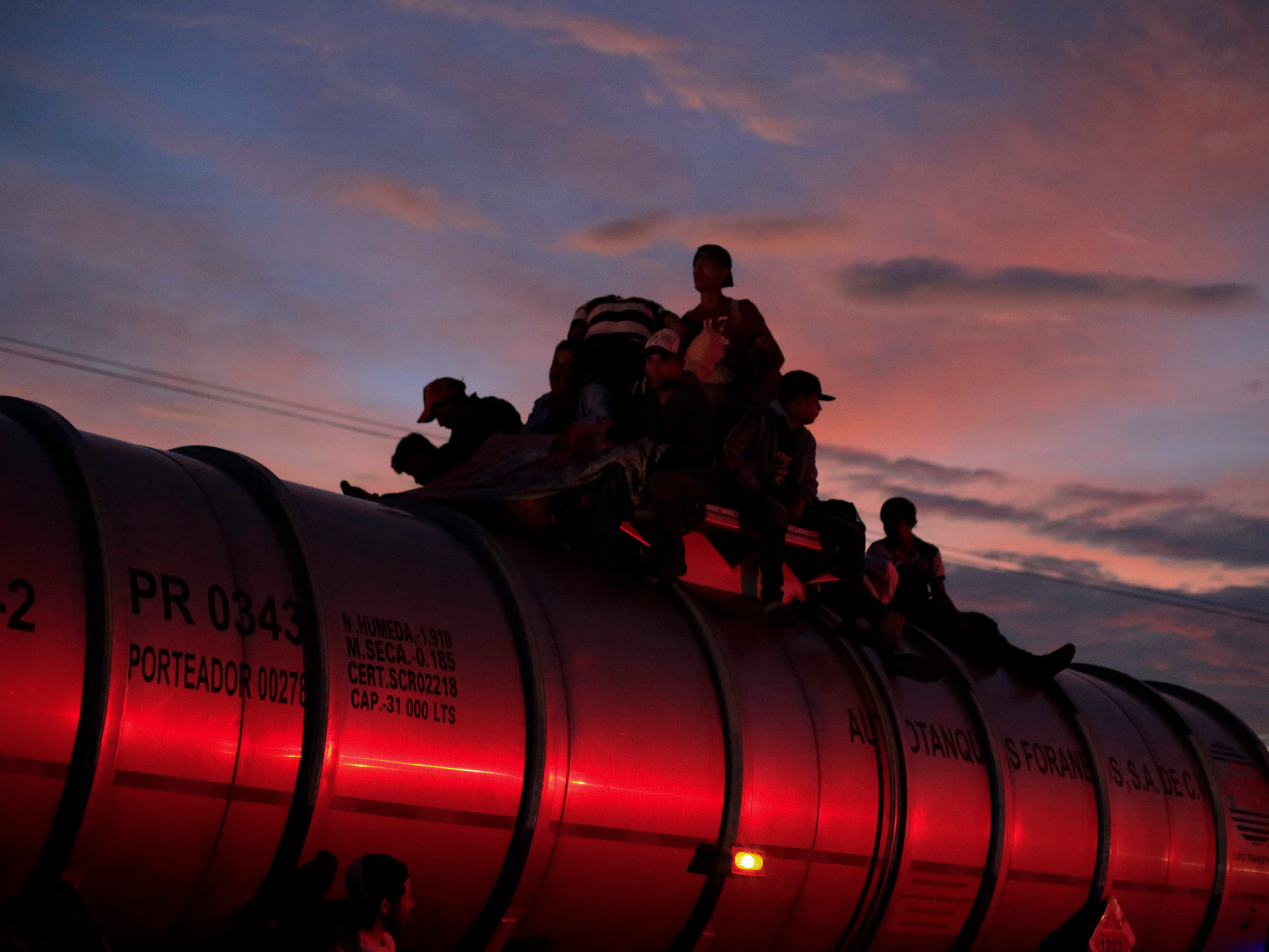 Migrants wait aboard a parked tanker in hopes that the driver will give them a ride, as a caravan of Central Americans continues its slow march toward the U.S. border, near Tapanatepec, Mexico, at dawn on Monday, Oct. 29, 2018. Thousands of migrants traveling together for safety resumed their journey after taking a rest day Sunday, while hundreds more migrants were pushing for entry to Mexico.
