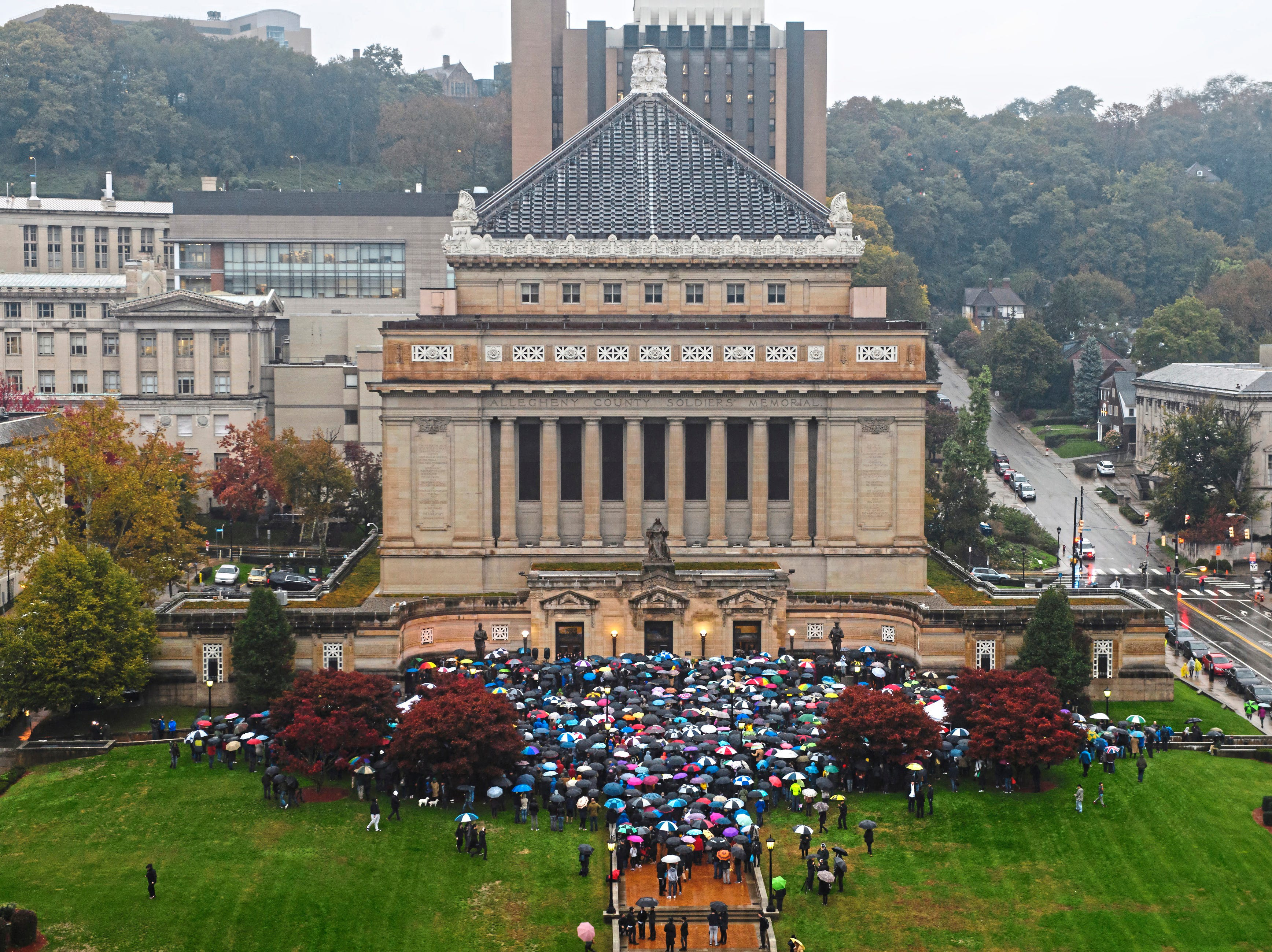 An overflow of people spill out of an interfaith community vigil, Sunday, Oct. 28, 2018, at Soldiers and Sailors Memorial Hall and Museum in Pittsburgh, organized by the Jewish Federation of Greater Pittsburgh, to honor those impacted by the previous day's mass shooting at Tree of Life Synagogue.