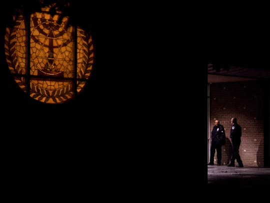 """Evansville police officers guard the front door of Temple Adath B'Nai Israel during the """"One God-One Community"""" interfaith program held at the synagogue in Evansville, Ind., Sunday, Oct. 28, 2018. According to Rabbi Mazo, there will be heightened security at the synagogue throughout the next week."""