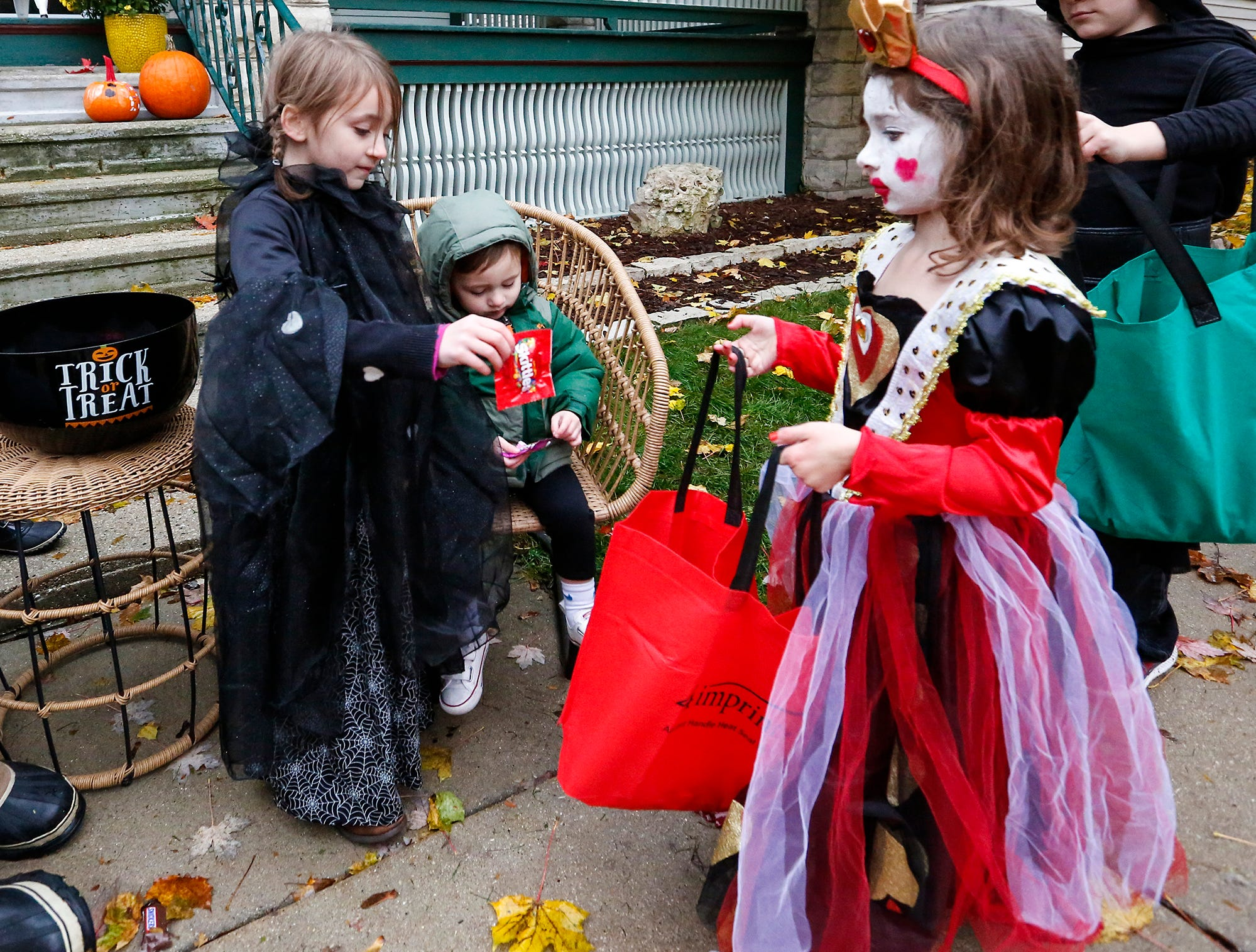 Honor and Wells Werdin hand out candy to Paige Bonney of Fond du Lac Sunday, October 28, 2018 during trick or treat in Fond du Lac, Wisconsin. Doug Raflik/USA TODAY NETWORK-Wisconsin
