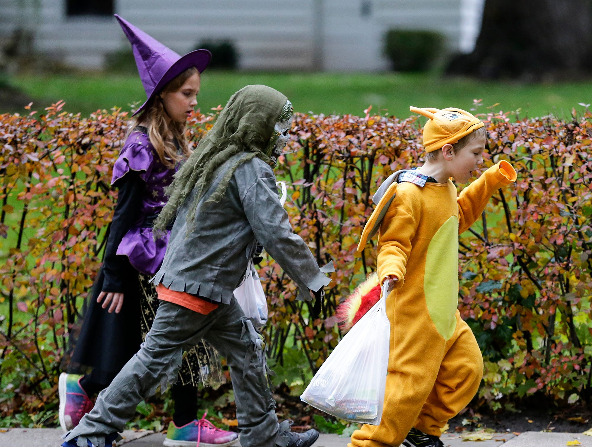 Maggie Burk, Damian Smith and Finnigan Burk of Fond du Lac were out trick or treating Sunday, October 28, 2018 in Fond du Lac, Wisconsin. Doug Raflik/USA TODAY NETWORK-Wisconsin