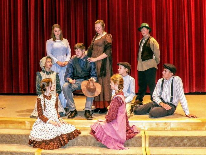 "Students rehearse for upcoming production of ""Caddie Woodlawn."" Woodlawn family: back row, from left – Laura Leclerc (Clara) of Glenbeulah, Elijah Gumness (Mr. Woodlawn) of Pickett, Annie Knowlton (Mrs. Woodlawn) of Waupun, Noah Gumness (Irish friend Robert Ireton) of Pickett; middle row – Helena Mucciolo (Caddie) of Ripon, Dawson Seibel (Warren) of Eldorado, Samuel Schmidt (Tom) of Fond du Lac; front row – Evelyn Holland (Minnie) of Fox Lake, Amarach Checolinski (Hetty) of Fond du Lac."