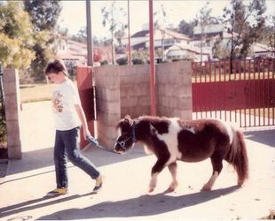 Christine Bragg leading T.D. on a walk at the Helen Woodward Animal Center in 1987. Bragg's time with T.D. established her love for miniature horses. She now breeds miniature horses in Idaho.