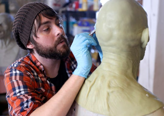 Jeff Cox, owner of The Basement FX, works on a zombie mask Oct. 24 in Milwaukee.