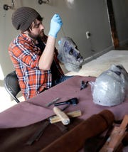 Jeff Cox, owner of The Basement FX in Milwaukee, works on a monster mask Oct. 24.