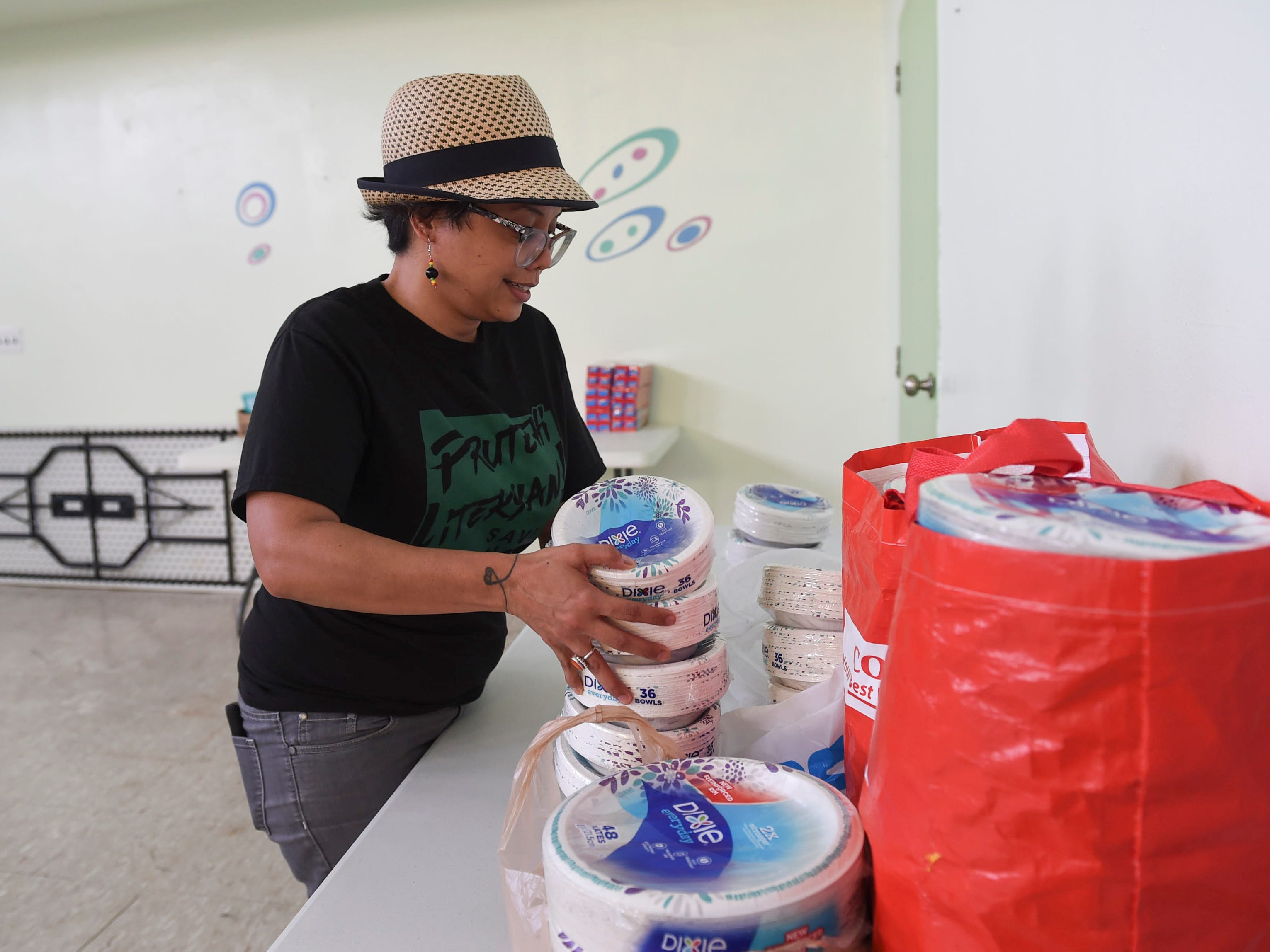 Monaeka Flores, a Prutehi Litekyan - Save Ritidian founding member, organizes donations of paper products at a Super Typhoon Yutu relief effort staging and distribution area on the San Vicente Catholic School campus, Oct. 29, 2018.
