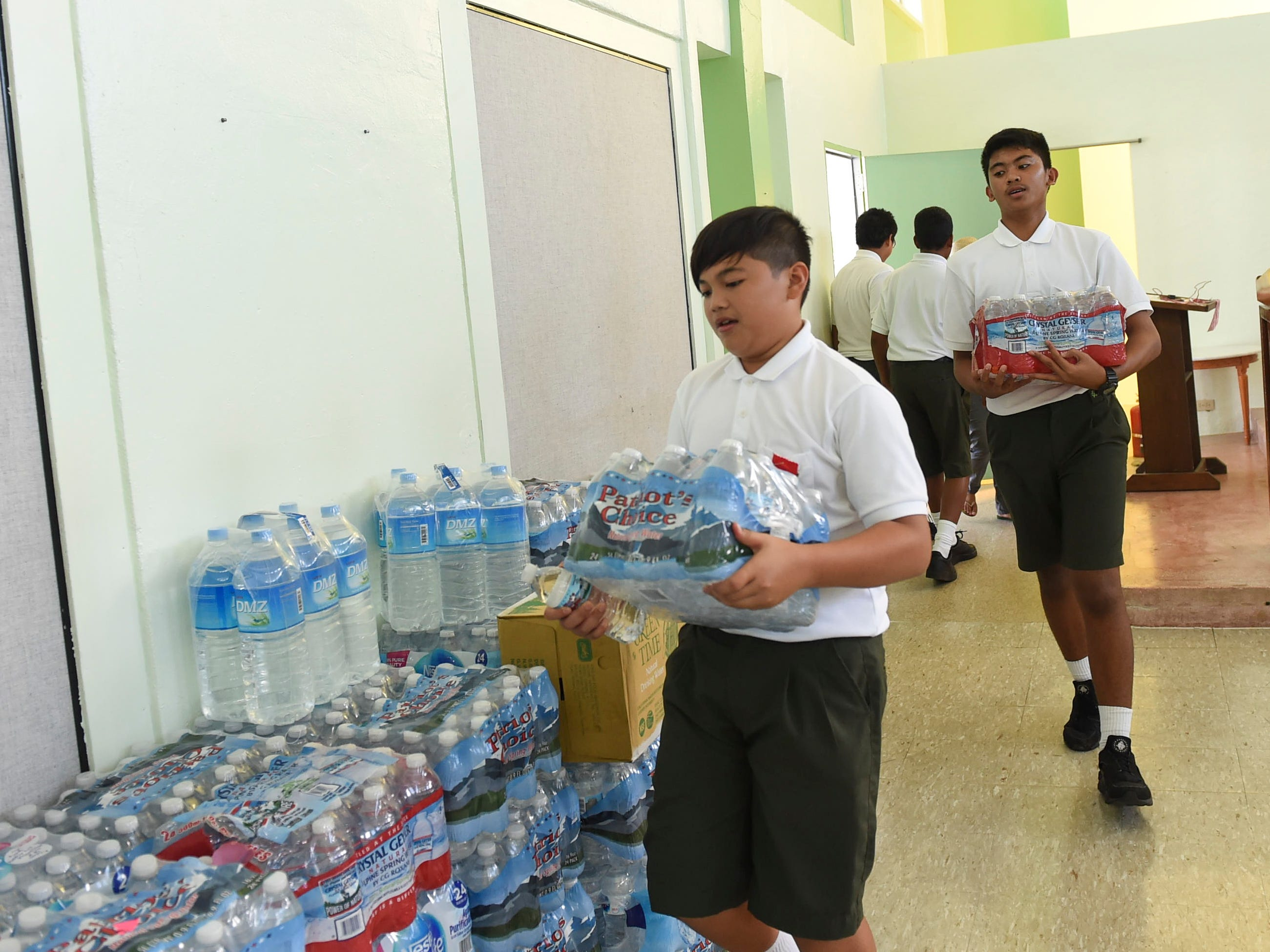 San Vicente Catholic School students Bryce Anthony Cruz Sablan, 12, front, and Joseph A. Mafnas, 13, help carry cases of bottled water for a Super Typhoon Yutu relief effort spearheaded by local organizations Prutehi Litekyan - Save Ritidian and Håya Foundation at the San Vicente Catholic School campus, Oct. 29, 2018.
