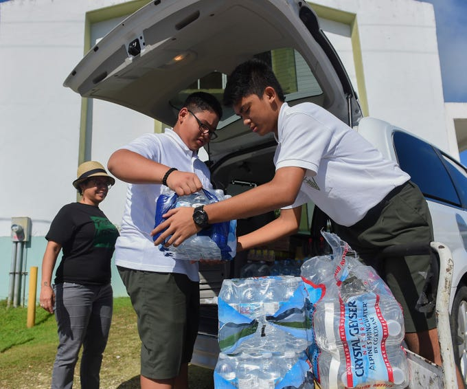 San Vicente Catholic School students Connor Leon Guerrero, 13, center, and Joseph A. Mafnas, 13, right, help unload cases of bottled water for a Super Typhoon Yutu relief effort spearheaded by local organizations Prutehi Litekyan - Save Ritidian and Håya Foundation at the San Vicente Catholic School campus, Oct. 29, 2018.