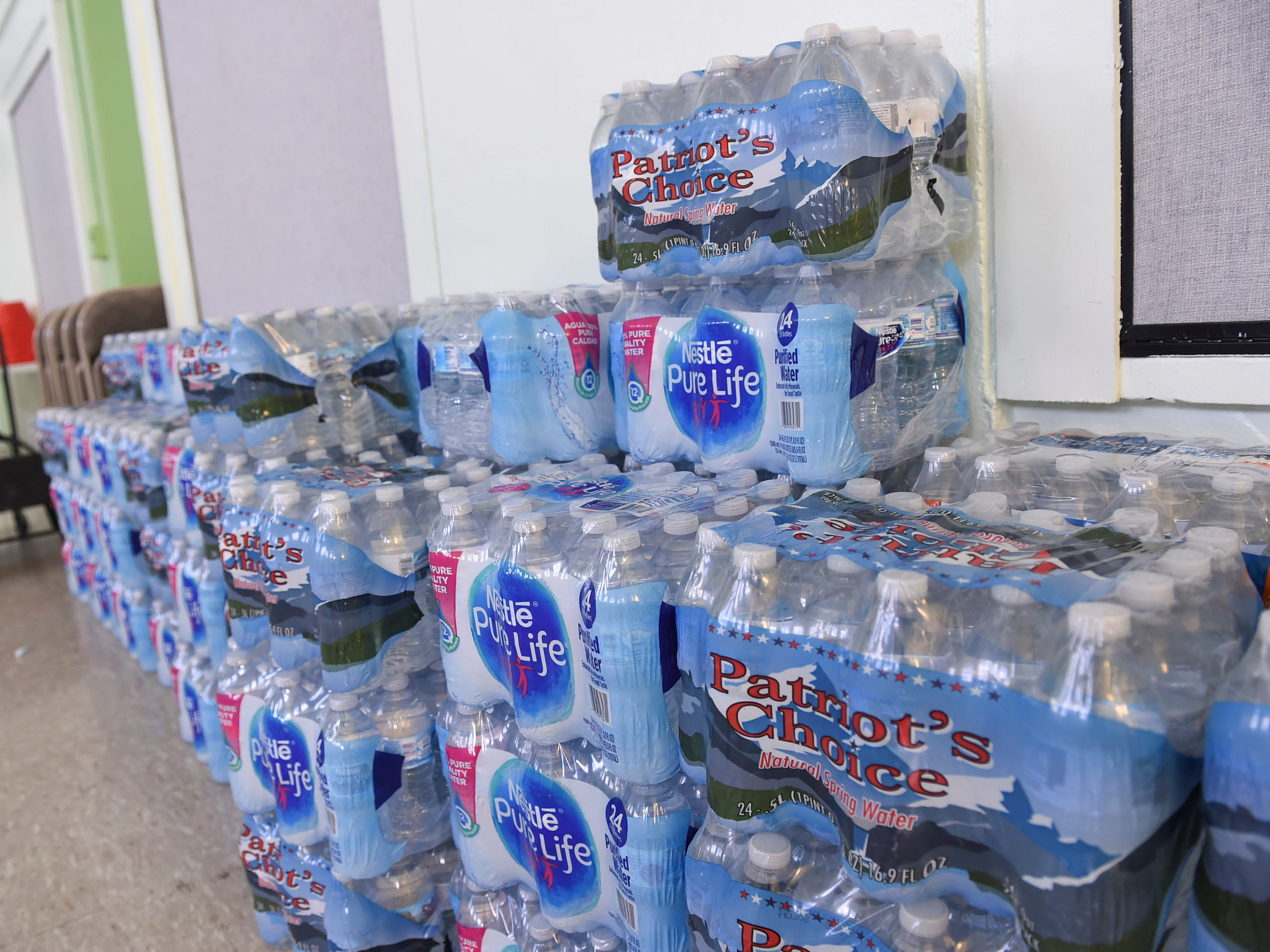 Donations of bottled water are stacked against the wall of a Super Typhoon Yutu relief effort staging and distribution area on the San Vicente Catholic School campus, Oct. 29, 2018.