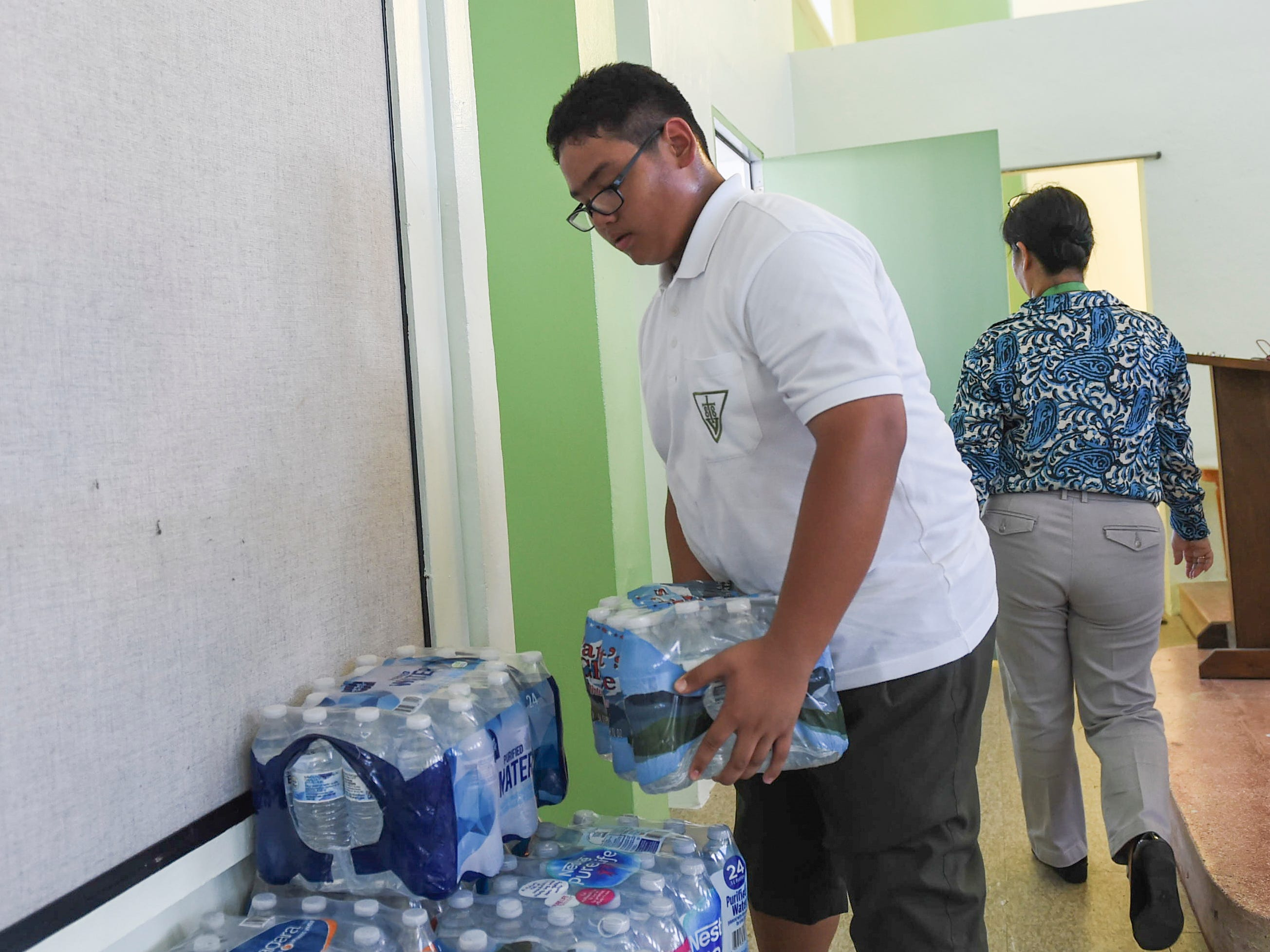 San Vicente Catholic School student Connor Leon Guerrero, 13, stacks cases of bottled water for a Super Typhoon Yutu relief effort spearheaded by local organizations Prutehi Litekyan - Save Ritidian and Håya Foundation at the San Vicente Catholic School campus, Oct. 29, 2018.