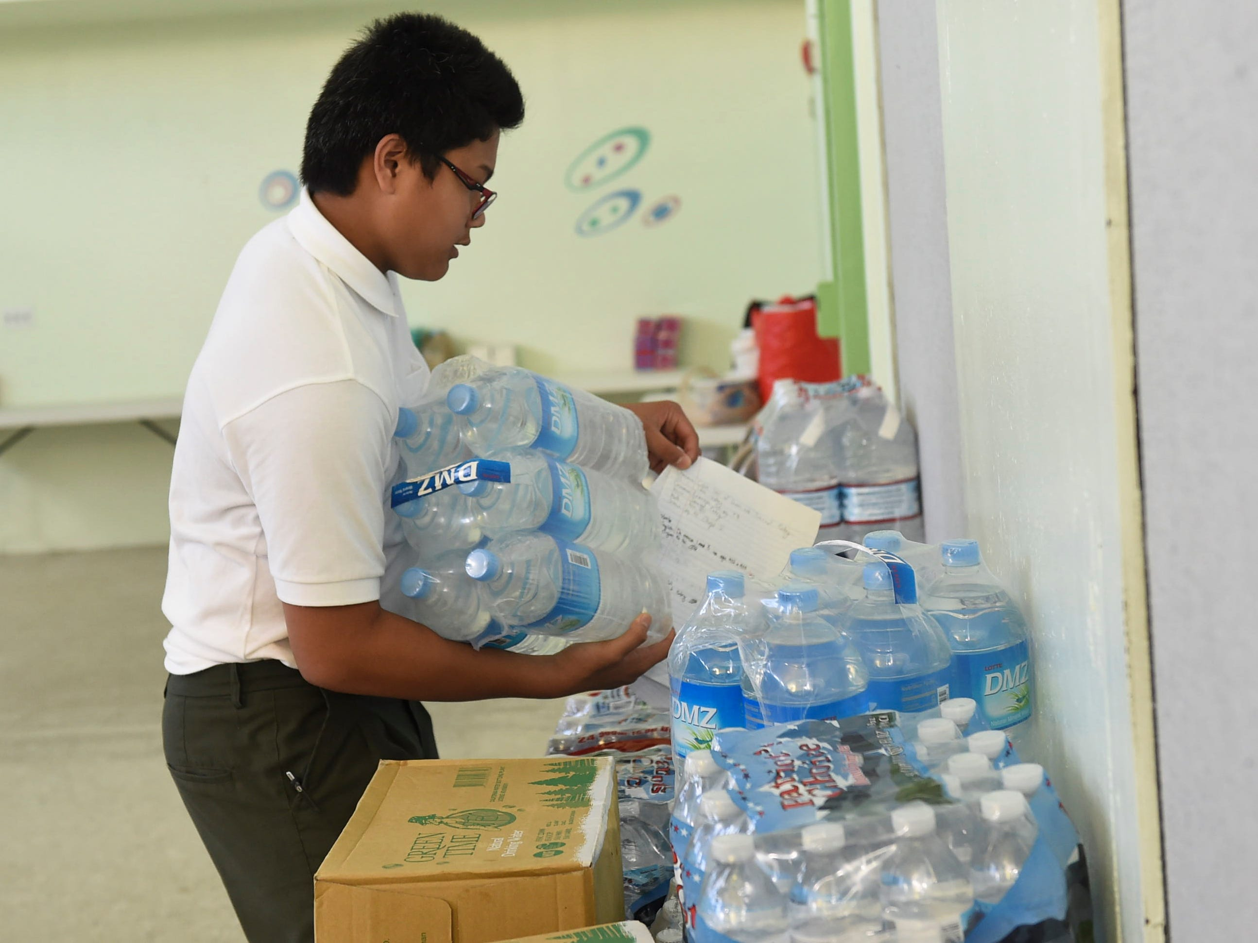 San Vicente Catholic School student Brendon C. Santos Cellona, 13, stacks a case of bottled water for a Super Typhoon Yutu relief effort at the San Vicente Catholic School campus, Oct. 29, 2018.