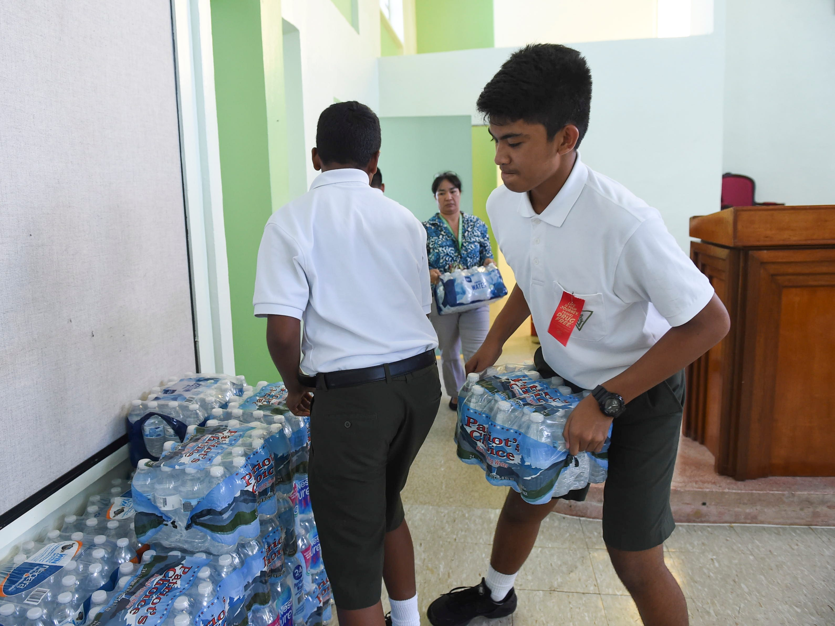 San Vicente Catholic School student Joseph A. Mafnas, 13, right, helps transport cases of bottled water to the staging and distribution area for a Super Typhoon Yutu relief effort on his school's campus, Oct. 29, 2018.