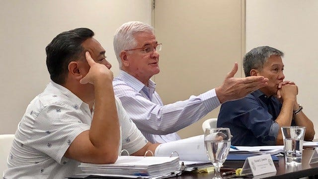 Guam Election Commission independent member Patrick Civille, center, gestures, as he addresses his colleagues during Monday night's meeting, while counsel Vincent Camacho, left, and Republican member Michael Perez look on.