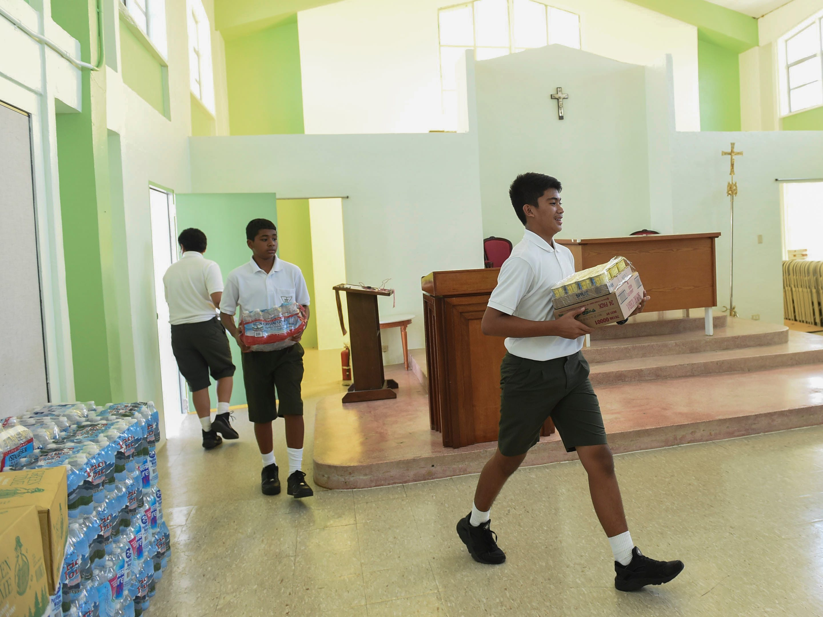 San Vicente Catholic School students Joseph A. Mafnas, 13, right, and Jamarion Santiago, 13, center, help transport donations of bottled water for a Super Typhoon Yutu relief effort spearheaded by local organizations Prutehi Litekyan - Save Ritidian and Håya Foundation at the San Vicente Catholic School campus, Oct. 29, 2018.